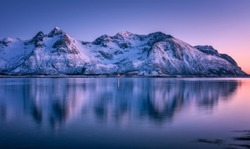Beautiful snow covered mountains and colorful sky reflected in water at dusk. Winter landscape with sea, snowy rocks, purple sky, reflection, at sunset. Lofoten islands, Norway at twilight. Nature