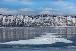 Beautiful snow formations on smooth glowing ice surface of frozen Baikal lake and covered with snow mountains on background, scenic winter landscape