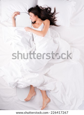 Beautiful snowboarder girl waiting for new season. Young woman sleeping and hugging snowboard. #226417267