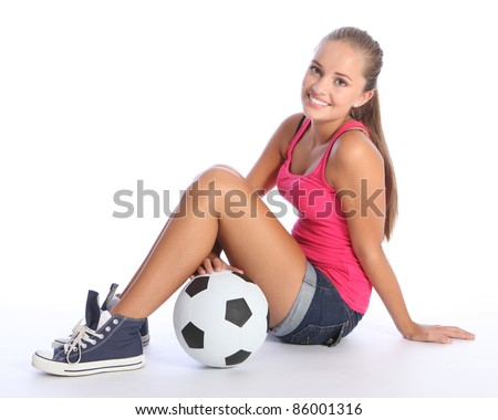 Beautiful soccer player teenage girl with happy smile wearing pink vest and denim shorts, sitting on floor with sports ball. Full body shot against white background.