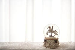 Beautiful sophisticated gift card. Vintage designed snow globe with a cute horse in it. Like a novel story. Copy space for your commercial. Christmas cover e-card.
