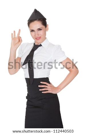 Beautiful sophisticated stylish stewardess making Ok hand gesture. Isolated on white