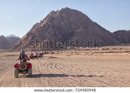Beautiful South Sinai desert landscape. Line of off road quads, mountains at background. Extreme sports & outdoors activities #734980948