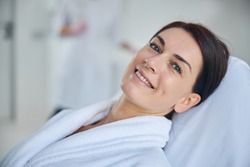 Beautiful spa client with a radiant smile posing for the camera in a wellness center
