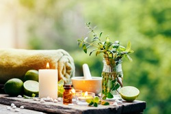 Beautiful spa composition with essential oil, fresh peppermint and burning candles on wooden table outdoors. Selective focus.