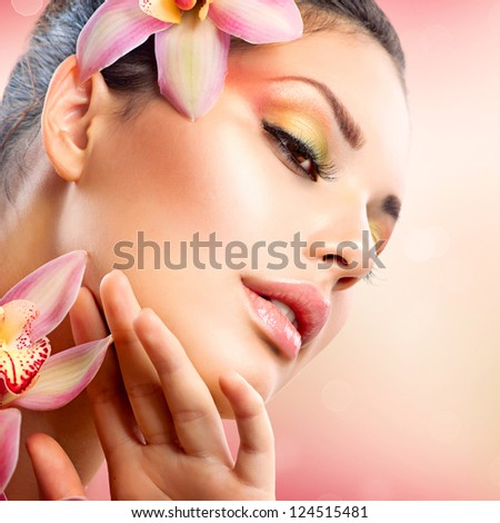 Beautiful Spa Girl With Orchid Flowers. Beauty Woman Touching her Face. Perfect Soft Skin. Skincare concept. Professional Make-up. Makeup