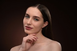 Beautiful spa model girl with perfect fresh clean skin and bare shoulders. Charming brunette model girl posing on camera touching her chin with a finger isolated on black background.