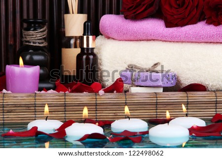 Beautiful spa setting near pool on bamboo background - stock photo