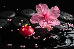 Beautiful spa setting of delicate pink hibiscus, zen stones with drops, candle and pearl beads on ripple water,  closeup