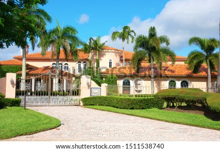 Beautiful Spanish style luxury mansion residential home with a privacy gate and palm trees on a blue sky sunny morning.