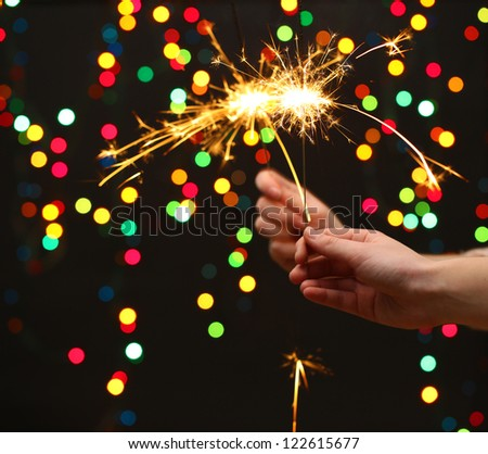beautiful sparklers in woman hands on garland background
