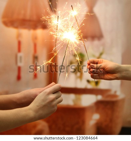 beautiful sparklers in woman hands on room background