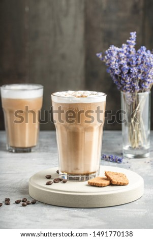 Beautiful speculoos latte with a foam of milk in a glass with coffee grains near it and some cookies. Lavender and another coffee in the back. Dark background Foto d'archivio ©