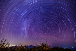 Beautiful spiral startrail at night.  Fantastic star timelapse with mountain background.