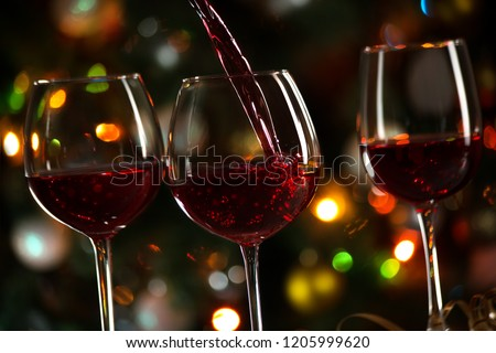 Beautiful splash of red wine on the background of Christmas lights