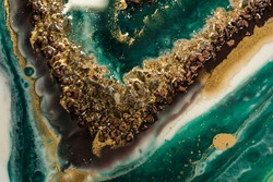 beautiful splashes of bronze stones and gold powder on streams of bright green, turquoise and gold resin, blurred waves. imitation of the cut of precious stones on an abstract background