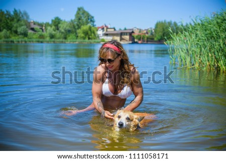 Beautiful sport fit woman playing with her corgi breed dog in at nature in countryside. Lifestyle portrait. Pet lover, dog owner #1111058171