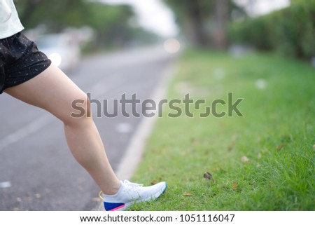 beautiful sport girl legs stand on wayside grass in morning before run with running shoe #1051116047