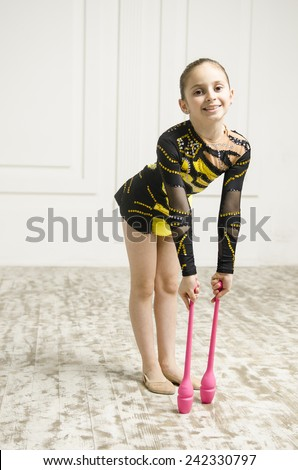 beautiful sport training rhythmic gymnastic girl with Rhythmic pink clubs doing professional exercises in white training room.