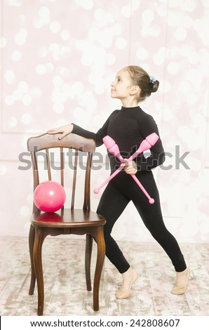 beautiful sport training rhythmic gymnastic girl with Rhythmic pink clubs doing professional exercises in white training room. sitting on wooden chair