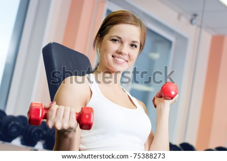 Beautiful sport woman doing power fitness exercise at sport gym. Dumbbell weight!