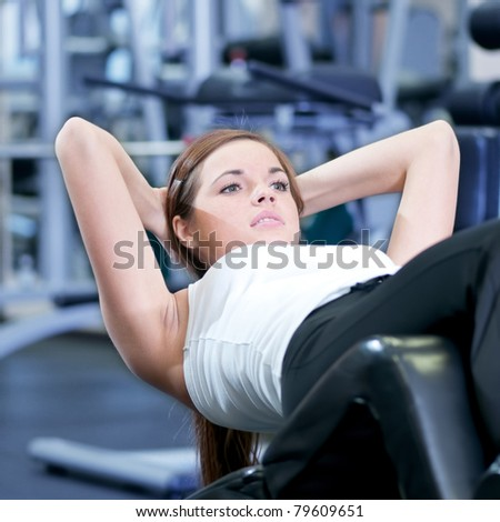 Beautiful sport woman doing press fitness exercise at sport gym