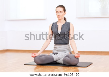 Beautiful sport woman doing stretching fitness exercise at sport gym. Yoga lotus pose - stock photo