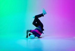 Beautiful sportive boy dancing hip-hop in stylish clothes on colorful gradient background at dance hall in neon. Youth culture, movement, style and fashion, action. Fashionable bright portrait.