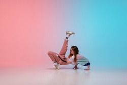 Beautiful sportive girl dancing hip-hop in stylish clothes on colorful gradient background at dance hall in neon light. Youth culture, movement, style and fashion, action. Fashionable bright portrait.