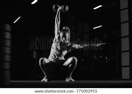 Beautiful sports and crossfit woman exercising at the gym doing overhead kettlebell squats copy space motivation beauty confidence fitness athletic body feminine powerful muscles weight gain concept