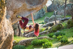 beautiful sports girl rock climber climbs the overhanging stone. bouldering in nature. sport climbing. fitness in nature.