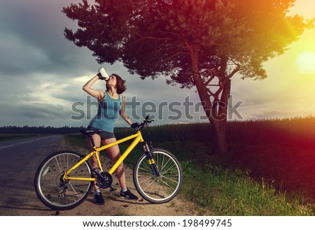 Beautiful sports girl with bike drinking water from a bottle. Style as instagram.