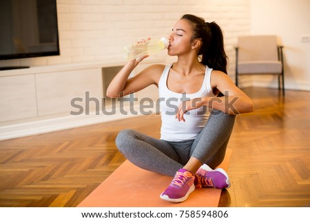 Beautiful sports woman drinking water while resting and sitting on yoga mat at home