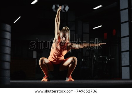 Beautiful sportswoman exercising at the gym doing overhead kettlebell squats copyspace motivation beauty confidence crossfit athletic body feminine powerful muscles weight gain concept. CrossFit woman