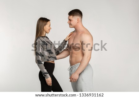 Beautiful sporty couple, sporty girl and muscular shirtless man posing in the studio looking at each other