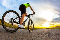 Beautiful sporty cyclist rides a bicycle on the road against the backdrop of beautiful nature and sunset. hobbies and sports