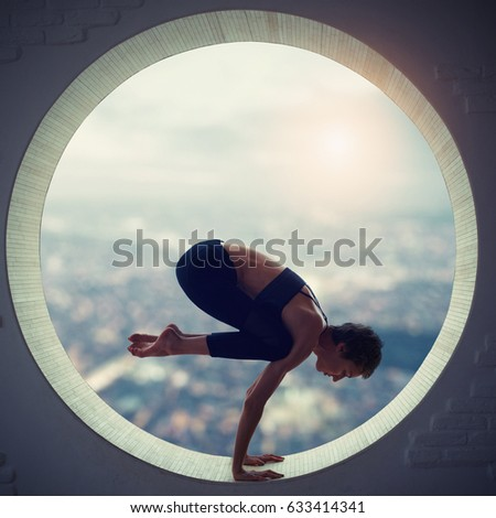 Beautiful sporty fit yogi woman practices yoga asana Bakasana - crane pose in a round window with a view of the city at sunset