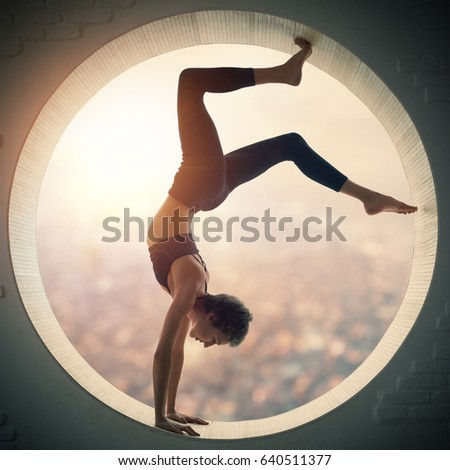 Beautiful sporty fit yogi woman practices yoga asana Bhuja Vrischikasana - Scorpion handstand pose in a round window with a view of the city at sunset