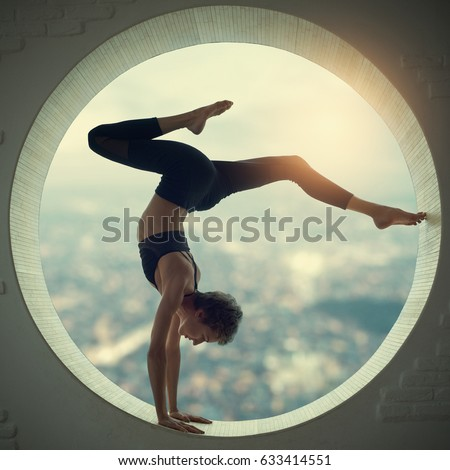 Beautiful sporty fit yogi woman practices yoga handstand asana Bhuja Vrischikasana - Scorpion handstand pose in a round window with a view of the city at sunset