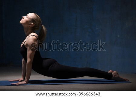 Beautiful sporty fit young woman in black sportswear working out indoors against grunge dark blue wall. Model doing urdhva mukha svanasana (sun salutation sequence asana). Full length. Copy space