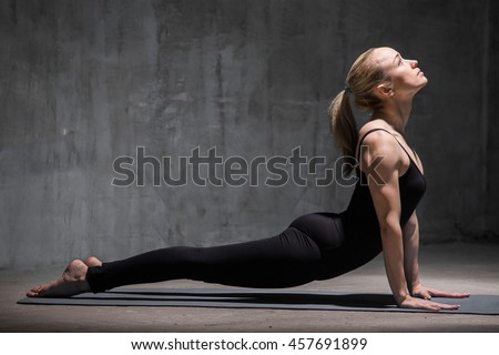 Beautiful sporty fit young woman in black sportswear working out indoors against grunge dark grey wall. Model doing urdhva mukha svanasana (sun salutation sequence asana). Full length. Copy space