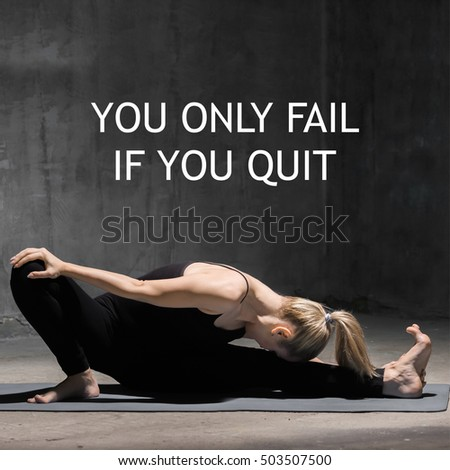 "Beautiful sporty fit young woman working out indoors against grunge dark grey wall. Model sitting in Head to Knee Forward Bend. Full length. Square image. Motivational text ""You only fail if you quit"""