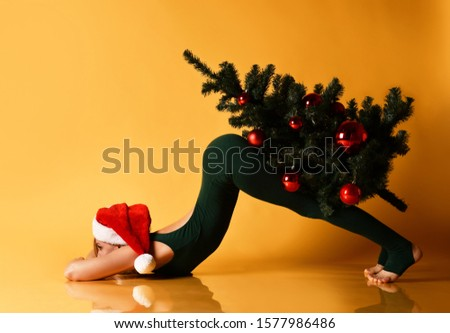 Beautiful sporty girl in a New Year hat does yoga asana stretching exercise holds and carry decorated Christmas tree. Healthy life fitness concept on yellow background