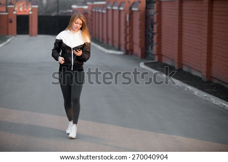 Beautiful sporty girl in sportswear walking in earphones during sport workout in the morning street holding device, looking at gadget, using app