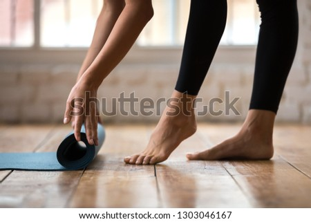 Beautiful sporty girl rolling blue exercise mat before or after working out at yoga studio or at home. Close up view of mat, hands and legs. Equipment for fitness, pilates, yoga. Concept of well being
