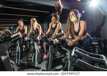 Beautiful sporty girls riding exercise bikes in gym. #1047499117