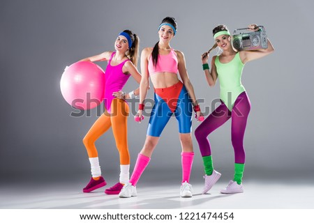 beautiful sporty girls with sports equipment and tape recorder smiling at camera on grey