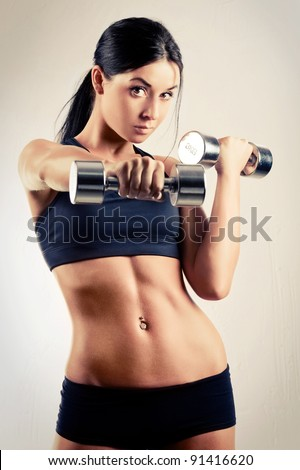 beautiful sporty muscular woman working out with two dumbbells