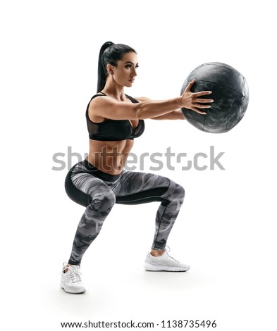 Beautiful sporty woman doing squats with med ball. Photo of muscular fitness model isolated on white background. Fitness and healthy lifestyle concept