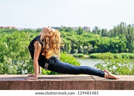 Beautiful sporty woman doing stretching exercise outdoors